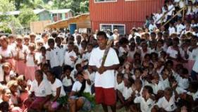 Head boy of Vura School in East Honiara, Solomon Islands holds the baton in front of students